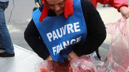 Demonstran membuka plastik berisi wortel ke jalanan depan kantor Kementerian Kesehatan di Paris, Rabu (4/10). Harga sebungkus rokok diperkirakan naik menjadi sekitar Rp 160 ribu perbungkus dari harga awal Rp 110 ribu. (AFP PHOTO/JACQUES DEMARTHON)