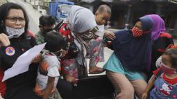 Perempuan dan anak-anak menaiki mobil bak terbuka untuk dievakuasi dari rumah mereka di lereng Gunung Merapi, di Krinjing, Jawa Tengah, Jumat (6/11/2020). Evakuasi dilakukan bagi warga lereng Merapi menyusul peningkatan status aktivitas vulkanik gunung tersebut. (AP Photo/Taufiq Rozzaq)