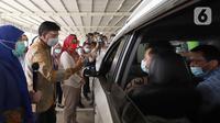 Menkominfo Johnny G. Plate (tengah) didampingi Presiden Direktur & CEO XL Axiata Dian Siswarini (kanan) dan Direktur Utama Rumah Sakit UI Astuti Giantini(kiri) meninjau vaksinasi untuk lansia Bangkit secara drive thru di Depok, Jawa Barat, Senin (5/4/2021). (Liputan6.com/Angga Yuniar)