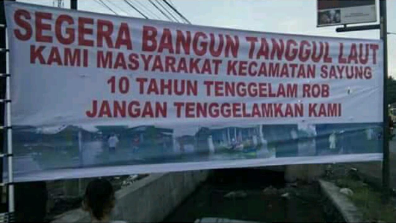 Warga memasang spanduk meminta agar Pemerintah Provinsi Jawa Tengah segera merealisasikan sabuk laut sebagai penahan rob. Program sabuk laut sudah direncanakan sejak jaman gubernur Bibit Waluyo, namun belum terlaksana. (foto: Liputan6.com/edhie prayitno i