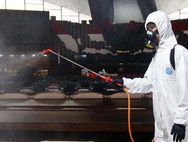 Petugas melakukan penyemprotan cairan disinfektan di area ruang rapat paripurna di Gedung Nusantara, Kompleks Parlemen MPR/DPR-DPD, Senayan, Jakarta, Minggu (29/3/2020). Penyemprotan ini dilakukan karena akan digelar rapat paripurna pada hari Senin, 30 Maret 2020. (Liputan6.com/Johan Tallo)