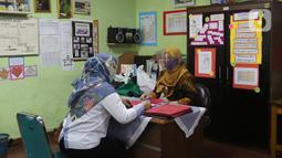 Guru membagikan laporan hasil belajar (rapor) kenaikan kelas kepada wali murid di SD Negeri Menteng 01 Jakarta, Kamis (25/6/2020). Pembagian dilaksanakan mengikuti protokol kesehatan COVID-19 serta membagikan rapor secara bertahap dari 24-26 Juni 2020. (Liputan6.com/Herman Zakharia)