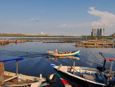 Nelayan melintasi area permukaan air laut yang menyurut di sekitar pesisir Kamal Muara, Kamis (15/3). Ketinggian air laut di sekitar dermaga semakin menurun yang menurut warga setempat akibat proyek reklamasi Pulau C dan D. (Merdeka.com/Iqbal S Nugroho)