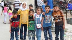 Anak-anak Suriah foto bersama di taman bermain sementara merayakan Idul Fitri, hari libur Muslim yang dimulai pada akhir bulan puasa Ramadhan, di Ariha di provinsi Idlib yang dikuasai pemberontak barat laut Suriah, (26/5/2020). (AFP Photo/Omar Haj Kadour)