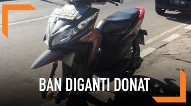 Betapa terkejutnya si pemilik motor saat dia mendapati ban motor bagian depannya hilang dan digantikan dengan donat.