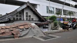 Kondisi sebuah rumah usang yang berada di halaman belakang apartemen Thamrin Executive Residence, Kebon Melati, Jakarta, Minggu (22/9/2019). Bertahan di tengah gedung pencakar langit membuat pemilik rumah, Lies (46), harus berebut air bersih dengan apartemen. (merdeka.com/Iqbal S Nugroho)