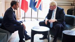 Presiden Prancis Emmanuel Macron berbincang dengan PM Inggris, Boris Johnson dalam kunjungan kenegaraan di Istana Elysee, Paris, Kamis (22/8/2019). Dalam pertemuan, Johnson tertangkap kamera bercanda ke arah kamera dan meletakkan kakinya di meja kopi. (Christophe Petit Tesson, Pool via AP)