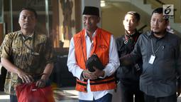 Bupati Kudus, Muhammad Tamzil (tengah) digiring petugas usai menjalani pemeriksaan terkait dugaan suap pengisian jabatan perangkat daerah di lingkungan Pemkab Kudus, Gedung KPK Jakarta, Sabtu (27/7/2019). KPK menyita barang bukti uang sebesar Rp170 juta. (Liputan6.com/Helmi Fithriansyah)