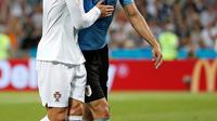 Penyerang Portugal, Cristiano Ronaldo memapah Penyerang Uruguay, Edinson Cavani yang Cedera keluar lapangan saat pertandingan babak 16 besar Piala Dunia 2018 di Stadion Fisht di Sochi, Rusia (30/6).  (AP Photo/Francisco Seco)