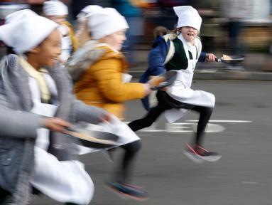 Anak-anak sekolah-sekolah lokal mengambil bagian dalam lomba lari sembari membawa wajan berisi pancake di Olney, Buckinghamshire, Inggris, Selasa (25/2/2020). Peserta kompetisi yang sudah ada sejak tahun 1445 ini harus membolak-balikan pancake sambil tetap berlari. (AP/Alastair Grant)