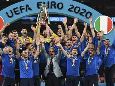 Para pemain Italia mengangkat trofi juara Euro 2020 usai mengalahkan Inggris pada pertandingan final di Stadion Wembley, London, Inggris, Minggu (11/7/2021). Italia menang 3-2 lewat adu penalti usai bermain imbang 1-1 di waktu normal. (Michael Regan/Pool via AP)