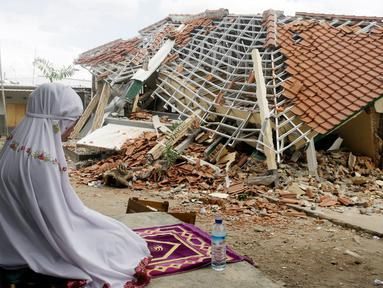 Seorang wanita berdoa di depan puing-puing bangunan di Lombok Barat, Nusa Tenggara Barat (NTB), Sabtu (11/8). BNPB menyatakan gempa Lombok hingga saat ini telah menewaskan 387 orang. (AP Photo/ Firdia Lisnawati)