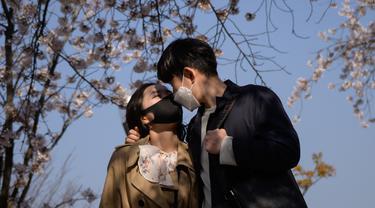 Pasangan mengenakan masker saat berdiri di bawah pohon yang mekar di Distrik Yeouido, Seoul, Korea Selatan, 5 April 2020. Organisasi Kesehatan Dunia (WHO) mengumumkan virus corona COVID-19 sebagai pandemi sejak 11 Maret 2020 lalu. (Ed JONES/AFP)
