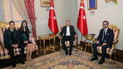 Gelandang Arsenal, Mesut Ozil didampingi kekasihnya Amine Gulse berbicang dengan Presiden Turki Recep Tayyip Erdogan saat menghadiri acara buka puasa bersama di Istana Dolmabahce, Istanbul, Turki (19/5). (Stringer/Turkish President's Press Office/AFP)