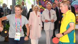 Pangeran Charles bersama istrinya Camilla Parker menonton atlet bermain tenis meja selama kunjungan ke desa atlet Goldwe Common Games 2018 di Gold Coast (5/4). (AFP Photo/Pool/William West)