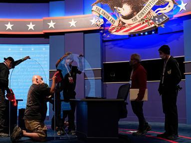 Pekerja membersihkan panel plastik pelindung di atas panggung di antara meja untuk Wakil Presiden Mike Pence dan penantangnya, Kamala Harris, saat persiapan untuk debat cawapres di Kingsbury Hall di Universitas Utah, Salt Lake City, Selasa (6/10/2020). (AP Photo/Patrick Semansky)