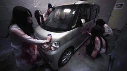 Para pemeran zombie membersihkan darah palsu pada kendaraan saat demonstrasi pertunjukan rumah hantu drive-in di Tokyo, Jepang, Selasa (18/8/2020). Rumah hantu drive-in ini diadakan di tengah pandemi COVID-19. (AP Photo/Eugene Hoshiko)