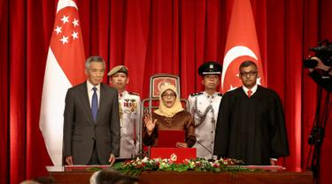Halimah Yacob mengambil sumpah jabatan saat berdiri bersama PM Singapura, Lee Hsien Loong (kiri) dan Ketua Hakim Sundaresh Menon saat peresmian menjadi Presiden Singapura di Istana Kepresidenan Singapura, (14/9). (Wallace Woon/Pool Photo via AP)