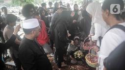 Keluarga menaburkan bunga di atas pusara mantan artis cilik Cecep Reza saat pemakaman di TPU Layur Penggilingan, Jakarta, Rabu (20/11/2019). Cecep Reza meninggal pada usia 31 tahun karena penyakit jantung. (Liputan6.com/Faizal Fanani)