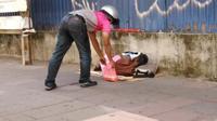 Seorang pengantar kiriman menaruh makanan untuk tunawisma di jalanan Kuala Lumpur (Dok.Facebook/We are Malaysians/https://web.facebook.com/357582290930791/photos/pcb.3011407092214951/3011399288882398/?type=3&theater)