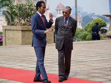 Presiden Joko Widodo berbincang dengan Perdana Menteri Malaysia Mahathir Mohamad usai upacara penyambutan resmi di Putrajaya (8/8/2019). Pertemuan membahas sejumlah isu dan upaya peningkatan kerja sama antara Indonesia dan Malaysia. (Farhan Abdullah/Department Of Information/AFP)