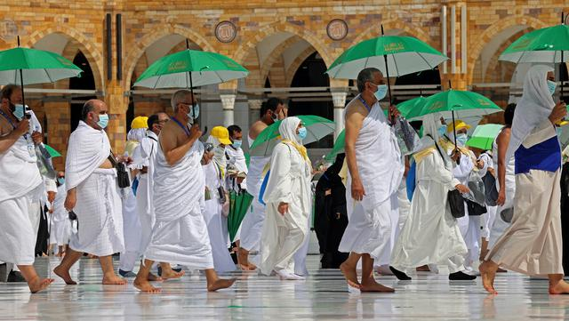Jemaah yang memegang payung untuk melindungi diri dari panas tiba di Masjidil Haram pada awal musim haji, Arab Saudi, Sabtu (17/7/2021). Pemerintah Arab Saudi mengklaim ibadah haji tahun lalu hanya diikuti 1.000 orang, sementara media lokal menyebut ada 10 ribu orang. (FAYEZ NURELDINE/AFP)