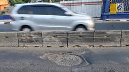 Kendaraan melintas di jalur bus Transjakarta yang rusak dan berlubang di Setia Budi, Jakarta, Selasa (30/7/2019). Minimnya pengawasan serta perawatan jalan oleh pihak terkait dapat mengakibatkan kecelakaan dan rusaknya bus Transjakarta. (merdeka.com/Iqbal S Nugroho)