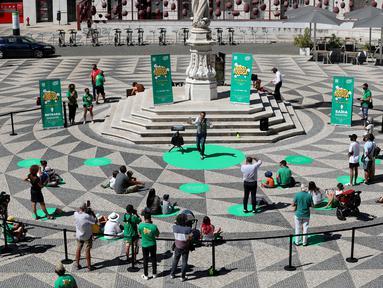 Para penonton menerapkan jaga jarak fisik saat menyaksikan pertunjukan sulap dalam Festival Dunia Sulap Jalanan Lisbon di Lisbon, Portugal (25/8/2020). Festival Dunia Sulap Jalanan Lisbon kedelapan dimulai pada Selasa (25/8). (Xinhua/Pedro Fiuza)