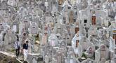 Sepasang warga mengunjungi makam kerabat saat Festival Chung Yeung atau juga dikenal Tomb Sweeping Day di sebuah pemakaman di Hong Kong, 17 Oktober 2018. Festival ini adalah hari untuk menghormati dan mengingat leluhur keluarga.  (Anthony WALLACE/AFP).