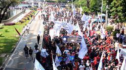 Massa buruh berjalan memasuki kawasan Jalan Medan Merdeka Barat, Senin (1/5). Aksi perayaan Hari Buruh Internasional oleh ribuan buruh tertahan di depan Kementerian Pariwisata akibat penutupan Jalan medan Merdeka Barat. (Liputan6.com/Helmi Fithriansyah)