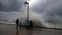 Warga berada di dekat ombak besar di Beirut, Lebanon (6/1). Badai kuat di Lebanon membawa suhu dingin dan salju ke pegunungan dan hujan lebat, angin kencang melanda pantai bagian dari negara Mediterania tersebut. (AP Photo/Bilal Hussein)