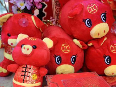 Boneka bertema Imlek dijual di kawasan Glodok, Jakarta, Kamis (31/1). Pernak-pernik Imlek bershio babi tanah sudah mulai ramai dijual. (Liputan6.com/Herman Zakharia)