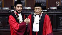 Ketua Mahkamah Konstitusi (MK) terpilih Anwar Usman (kiri) berjabat tangan dengan Wakil Ketua terpilih Aswanto usai acara pengucapan sumpah jabatan Ketua dan Wakil Ketua MK di gedung MK, Jakarta, Senin (2/4). (Liputan6.com/Immanuel Antonius)
