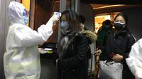 Petugas kesehatan berjas Hazmat memeriksa suhu tubuh penumpang yang datang dari kota Wuhan di bandara Beijing (22/1/2020). Virus corona jenis baru ini ditemukan pertama kali di Wuhan, Provinsi Hubei, Tiongkok. Virus ini diyakini berasal dari pasar makanan laut segar di Wuhan. (AP Photo/Emily Wang)