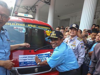 PLT Gubernur DKI Jakarta Soni Sumarsono (kanan) menempelkan stiker integrasi Transjakarta-Koperasi Wahana Kalpika (KWK) saat peresmian di Halaman Balaikota, Jakarta, Senin (3/4). (Liputan6.com/Faizal Fanani)