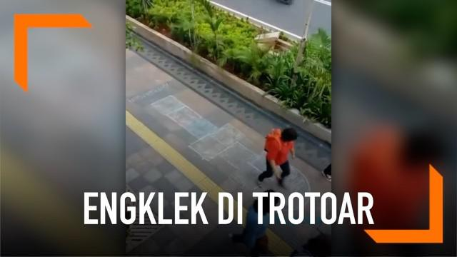 Para pejalan kaki di Jalan Sudirman, Jakarta mendadak bermain engklek. Hal ini terjadi karena trotoar digambari kotak bermain.