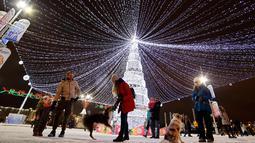Pengunjung bermain dengan anjing di samping pohon tahun baru dengan dekorasi untuk menyambut Natal 2018 dan Tahun Baru 2019 di Octyabrskaya Square, Minsk, Belarus, Selasa (18/12). (AP Photo/Sergei Grits)