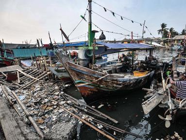 Aktivitas nelayan di dekat tumpukan sampah di Kampung Nelayan Cilincing, Jakarta Utara, Selasa (8/6/2021). Berdasarkan data  TKN PSL Kementerian Koordinator Kemaritiman dan Investasi, total sampah yang masuk ke laut Indonesia tahun 2020 diperkirakan 521.540 ton. (merdeka.com/Iqbal S. Nugroho)