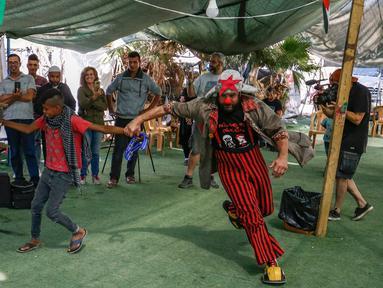 Rombongan badut Spanyol menghibur anak-anak Palestina di desa suku Bedouin, Tepi Barat yang diduduki, 22 September 2018. Atraksi ini dilakukan lantaran desa berpenduduk sekitar 180 orang itu akan digusur Israel pada Oktober mendatang. (AFP/ABBAS MOMANI)