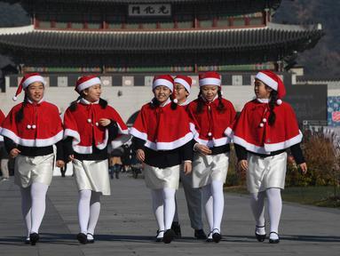 Anak-anak Korea Selatan mengenakan pakaian Santa Claus berjalan di depan Istana Gyeongbokgung, Seoul, Jumat (30/11). Anak-anak tersebut bersiap meluncurkan kampanye penggalangan dana akhir tahun dari The Salvation Army. (Jung Yeon-je/AFP)