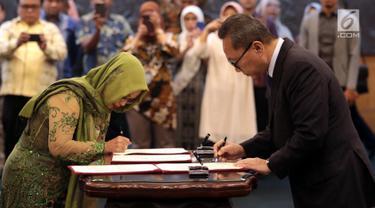 Ketua MPR Zulkifli Hasan (kanan) menandatangani dokumen saat melantik empat anggota MPR Pengganti Antar Waktu (PAW) di Kompleks Parlemen, Jakarta, Kamis (14/3). Anggota MPR PAW akan bekerja pada sisa masa jabatan Tahun 2014-2019. (Liputan6.com/JohanTallo)