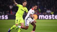 Duel antara Memphis Depay dan Ivan Rakitic pada leg 1, babak 16 besar Liga Champions yang berlangsung di stadion Parc Olympique Lyonnais, Lyon, Rabu (20/2). Barcelona bermain imbang 0-0 kontra Lyon. (AFP/Franck Fife)