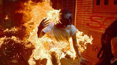 Seorang demonstran terbakar saat unjuk rasa menentang Presiden Venezuela, Nicolas Maduro di Caracas, Rabu (3/5). Pria tersebut tersulut api dari ledakan tangki sepeda motor milik polisi saat unjuk rasa yang diwarnai bentrokan. (RONALDO SCHEMIDT / AFP)