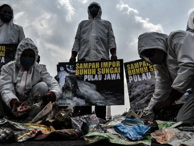 """Aktivis membawa poster saat aksi """"Sampah Impor Bunuh Sungai Pulau Jawa"""" di kawasan Patung Kuda, Monas, Jakarta, Senin (3/5/2021). Aktivis tergabung dalam Ecoton dan Forkadas (Forum Komunitas Daerah Aliran Sungai Citarum, Ciujung, serta Ciliwung Institut). (merdeka.com/Iqbal S. Nugroho)"""