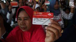 Warga menunjukkan KKS saat Penyaluran Bantuan Sosial PKH dan BPNT di Depok, Jawa Barat, Selasa (12/2). Jumlah bantuan PKH dan BPNTmencapai Rp.70.558.785.000 yang terdiri Rp26.460.225.000  untuk 21.374 KPM PKH. (Liputan6.com/Herman Zakharia)