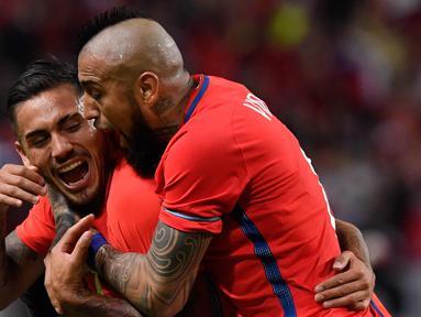 Penyerang Chile, Marcos Bolados (kiri) melakukan selebrasi dengan rekannya Arturo Vidal usai mencetak gol ke gawang Swedia pada pertandingan persahabatan internasional di Friends Arena, Stockholm, (24/3). Chile menang 2-1. (Anders Wiklund/TT via AP)