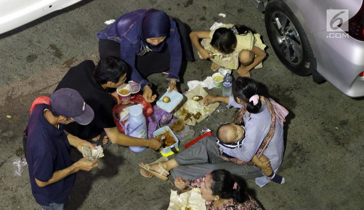 Pemudik makan bersama sambil menanti waktu masuk kapal di Dermaga II Pelabuhan Penyebrangan Merak, Banten, Senin (3/6/2019). Sambil menanti waktu bongkar muat kapal penyebrangan, pemudik memanfaatkan waktu untuk makan bersama. (Liputan6.com/Helmi Fithriansyah)