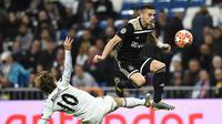 Dusan Tadic mencoba melewati hadangan Luka Modric pada laga leg kedua, babak 16 besar Liga Champions yang berlangsung di Stadion Santiago Bernabeu, Madrid, Rabu (6/3). Real Madrid kalah 1-4 kontra Ajax. (AFP/Gabriel Bouys)