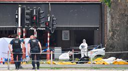 Polisi melakukan penyelidikan di lokasi penembakan di Liege, Belgia (29/5). Pelaku awalnya menusuk kedua polisi dari belakang menggunakan pisau lalu merampas pistol mereka dan menembak kedua polisi serta seorang pejalan kaki. (AP/Geert Vanden Wijngaert)