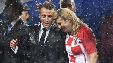 Presiden Prancis Emmanuel Macron (kiri) berbicara dengan Presiden Kroasia Kolinda Grabar-Kitarovic usai laga final Piala Dunia 2018 antara Prancis dan Kroasia di Stadion Luzhnik, Moskow, Rusia, Minggu (15/7). (Franck Fife/AFP)
